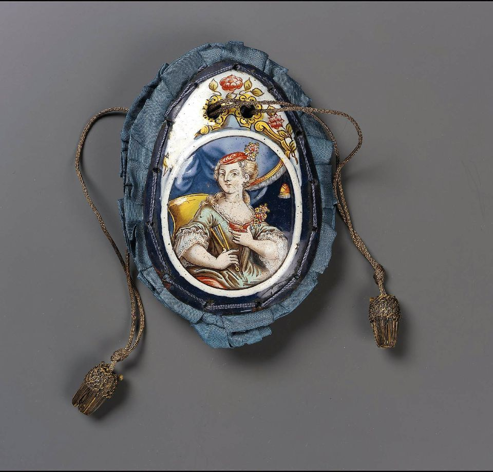 Late 17th-early 18th century, France - Drawstring bag - Blue silk taffeta eith 2 enameled metal plaques (one with man, other with woman, in costume of 1700-15) edged with pleated silk ruffle. Yellow metallic drawstring.