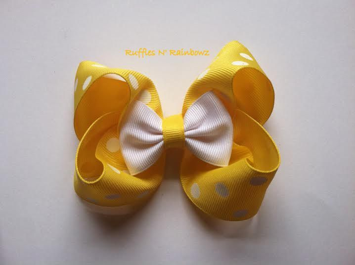 Hair bow from Ruffles N' Rainbowz.  Pictured is a Loopy bow stacked with a bow tie.  Send us a message on FB to order.