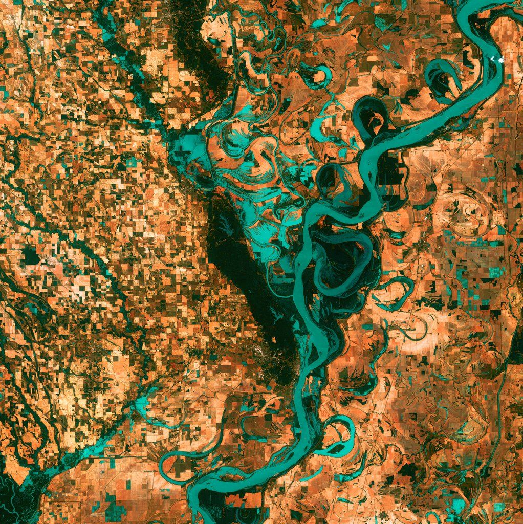 the Mississippi, the largest river system in north america, is shown snaking through towns, fields , and pastures south of Memphis, Tennessee