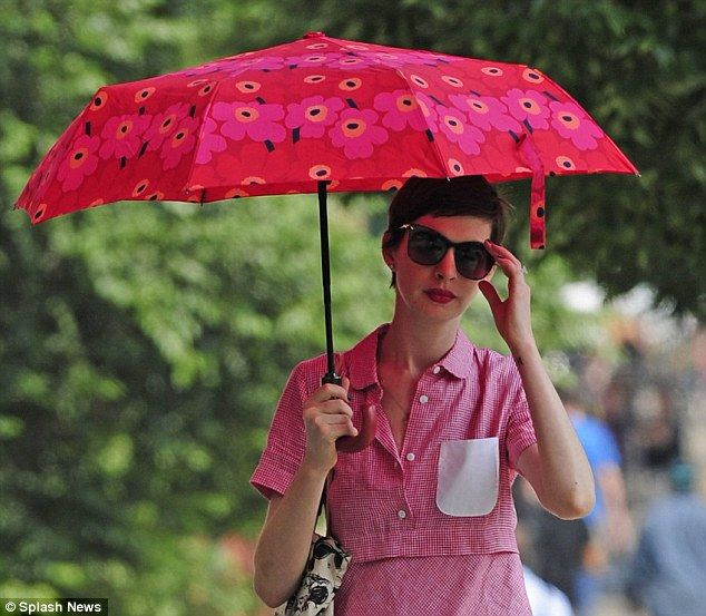 How to stay pale and interesting... Anne Hathaway protects her delicate skin from the summer sun with a parasol as she takes a walk in New York City #largeumbrella