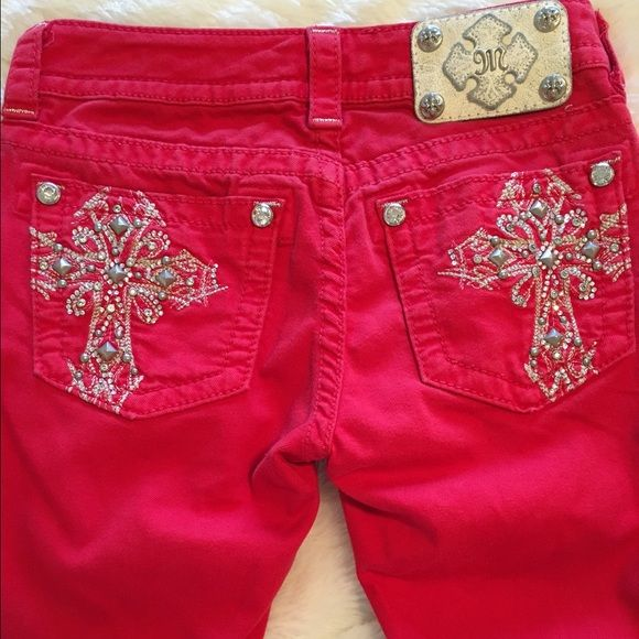 """Bright Red Miss Me Rhinestone Cross Skinny Jeans Gorgeous bright red Miss Me rhinestone cross pocket skinny jeans. Size 25. 4th pic shows some dark staining (3 different spots) from wash... Could be the beginning of a tie dye Price reflects flaw. All else is in great condition. All stones intact. Waist 12.5"""", Rise 7"""", Inseam 32"""". 2% elastane. ❌ NO TRADES ❌ NO LOWBALLING ❌ Miss Me Jeans Skinny"""