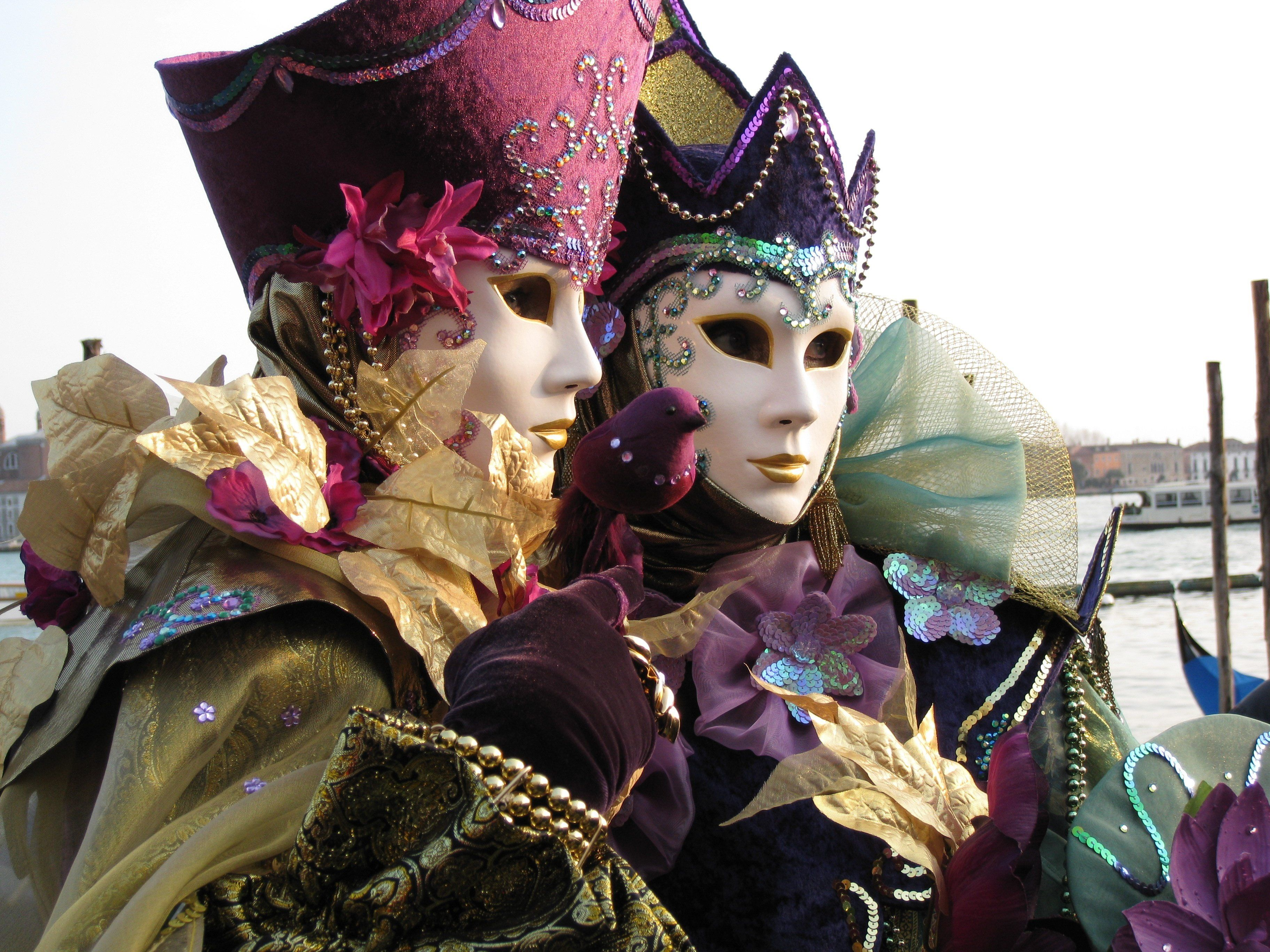 Venetian Carnival. Two women pose in elaborate costumes beside the canal.