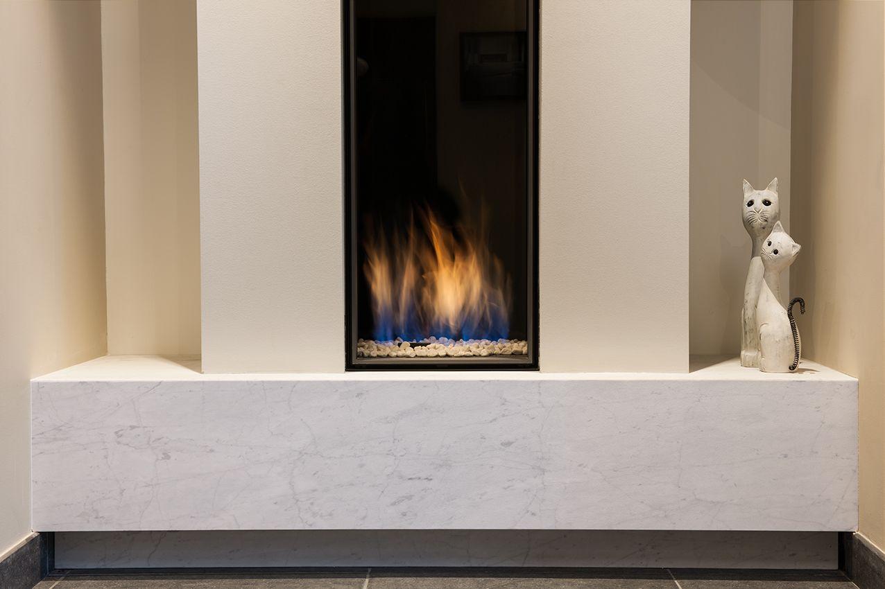 toonzaal - showroom Alpha Heating - Schoten (Antwerpen): Bellfires Vertical Bell Medium 3 in strakke schouwmantel, onderaan afgewerkt met natuurstenen plateau (Carrara-marmer, gezandstraald)