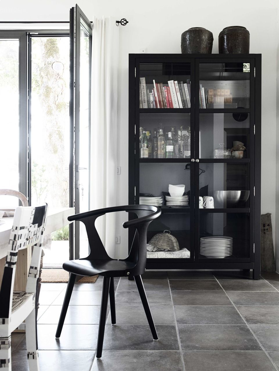 Modern Dining Room With A Black China Cabinet Containing Books Tableware And Alcohol