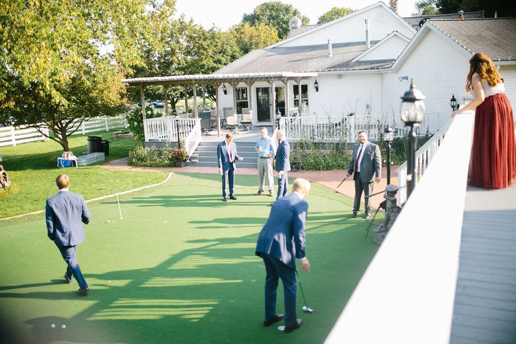 The groom and his groomsmen are having fun on the putting ...