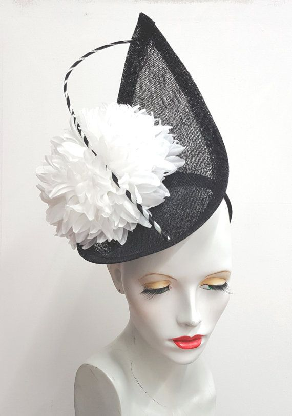 b5976c2a45c35 A large black teardrop shape has been blocked in sinamay, the edge wired  and bound. Topped with a large white fabric chrysanthemum flower and a white  and ...