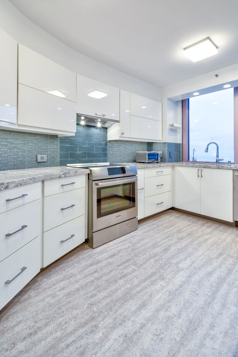 Modern Kitchen Renovation With High Gloss White Cabinets Quartz Countertops And Vinyl Plank Floor Modern Kitchen Renovation Custom Homes Custom Home Builders