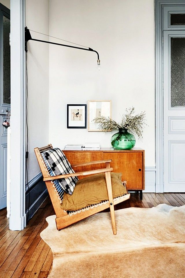 Living room with french blue mouldings, a buffalo plaid chair, and a midcentury sconce