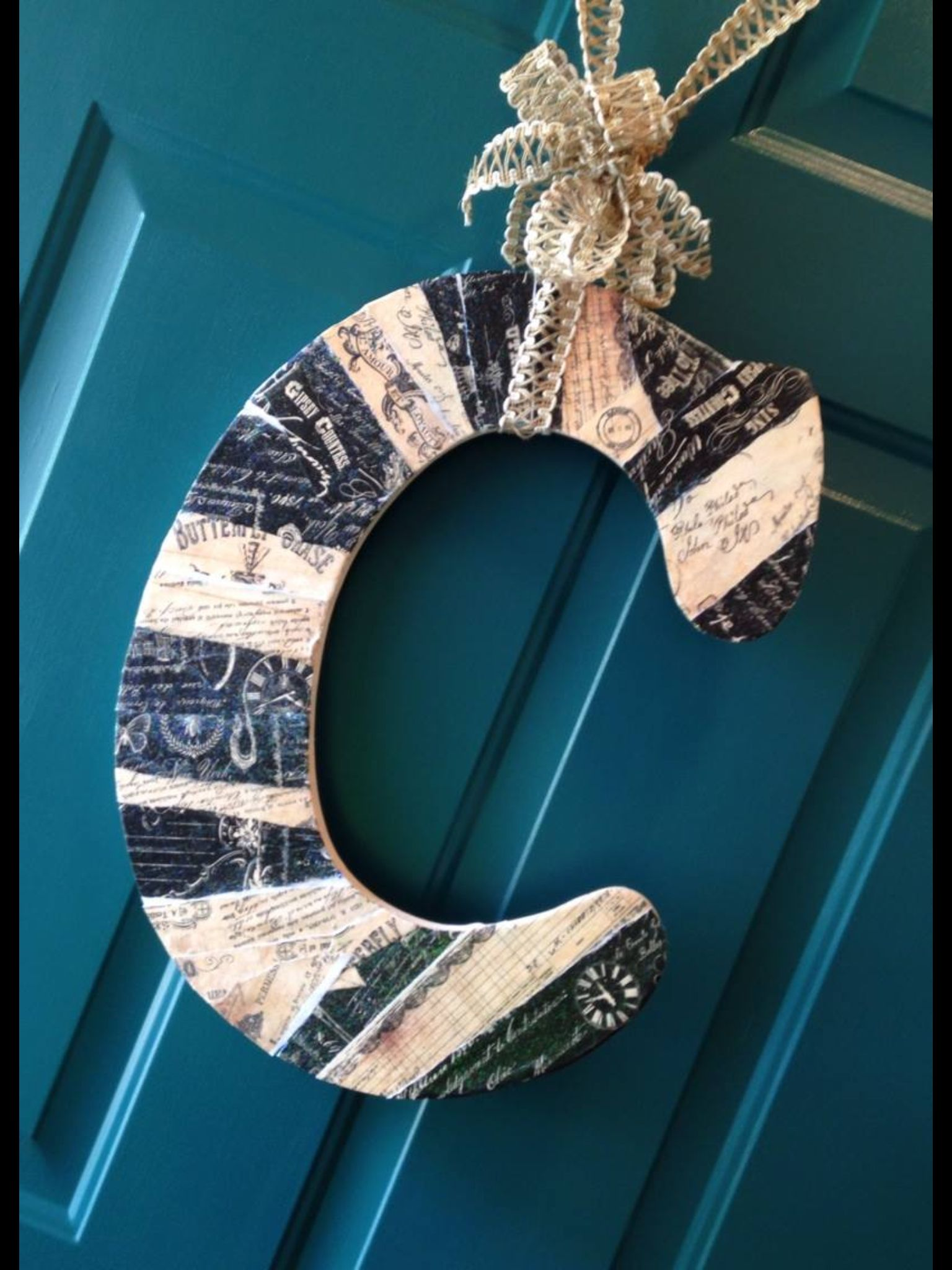Wooden initial covered in strips of vintage paper.