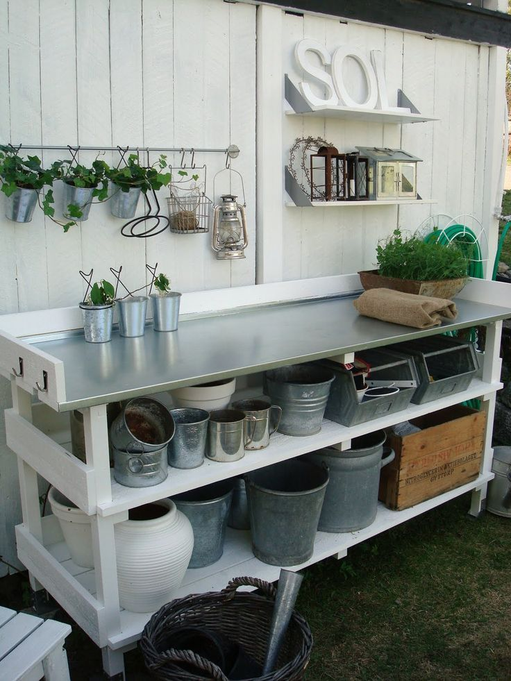 Photo of outdoor planting station with stainless steel counter shelving and hooks