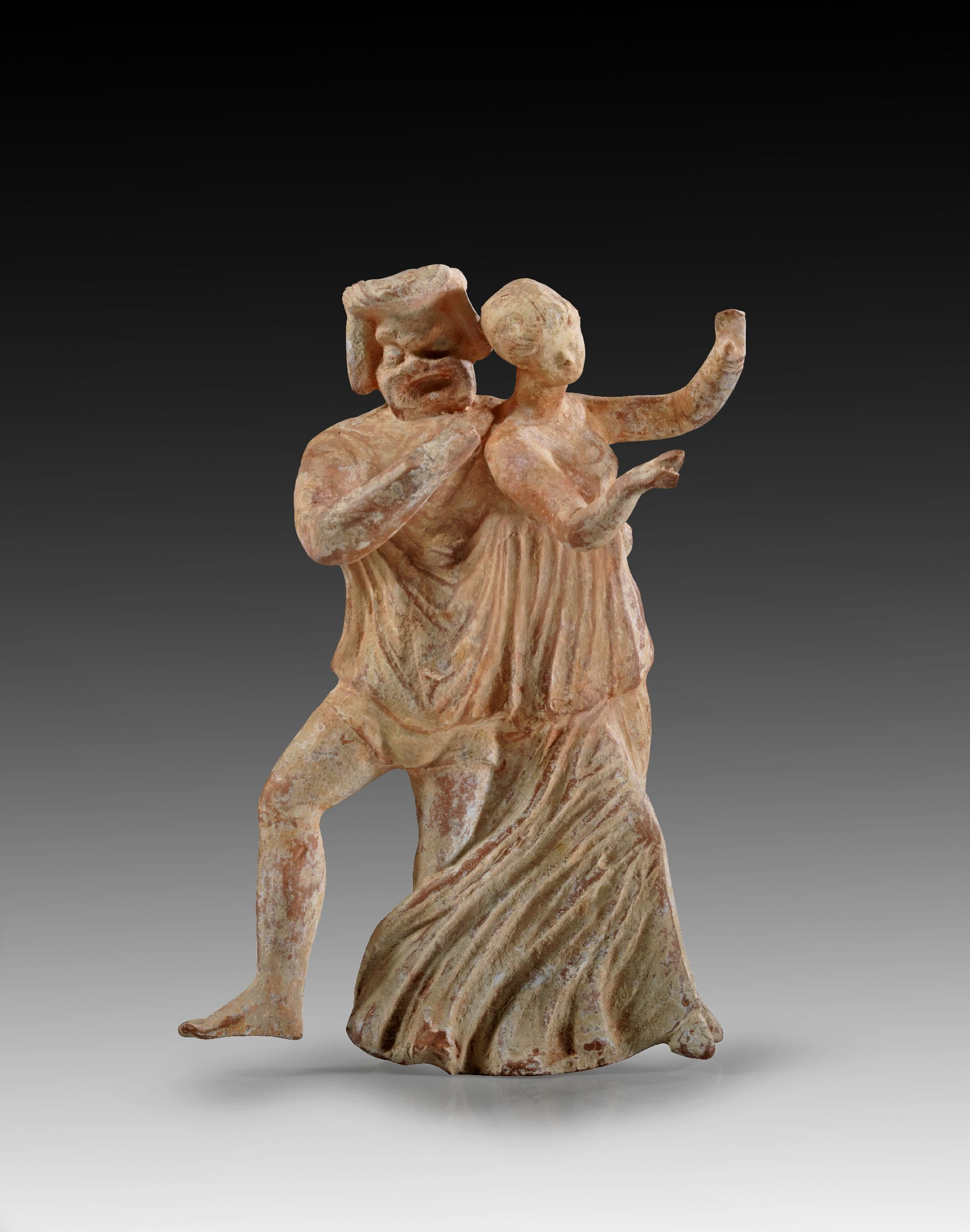 Terracotta phlyax with large mask and girl wearing chiton standing next to each other. The phlyax putting his arm around the girls waist. With traces of white slip and pink painting. Magna Graecia, 3rd - 2nd century B.C. The arms, the phlyax leg and both heads are reattached.