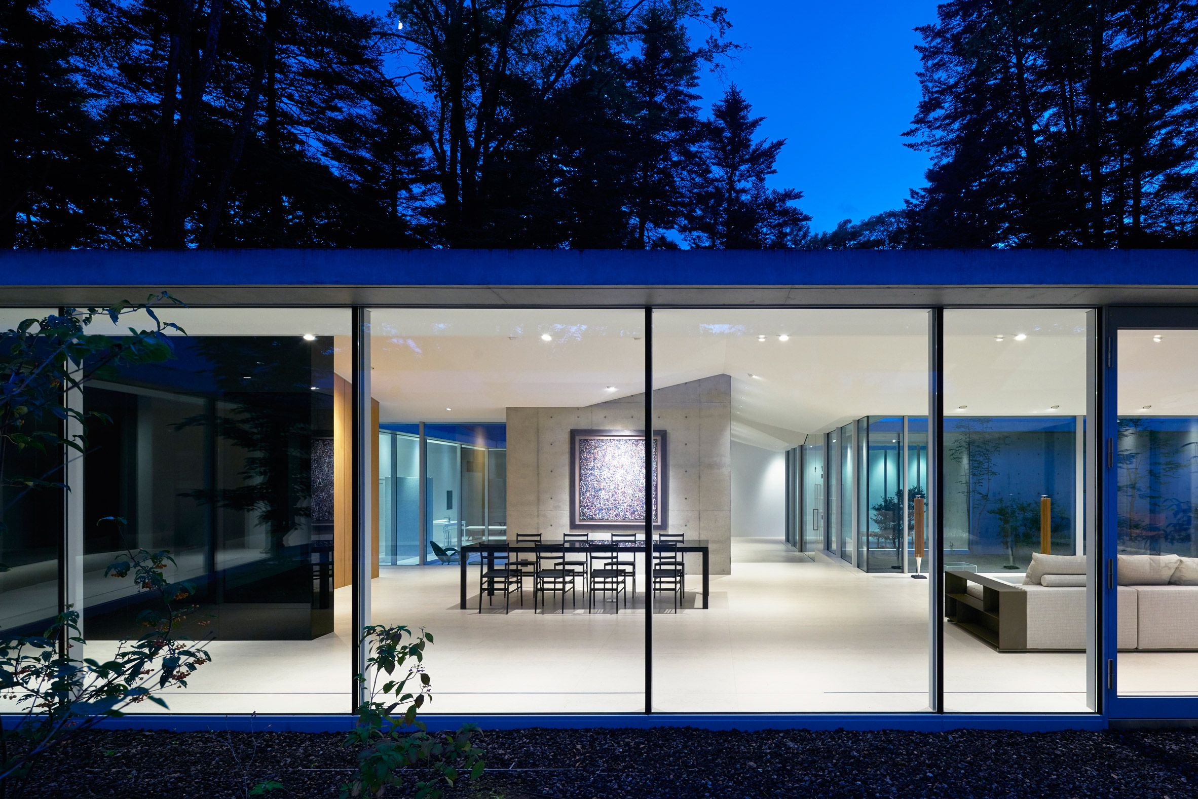 Enclosed courtyards frame views of trees and sky at house in a ...