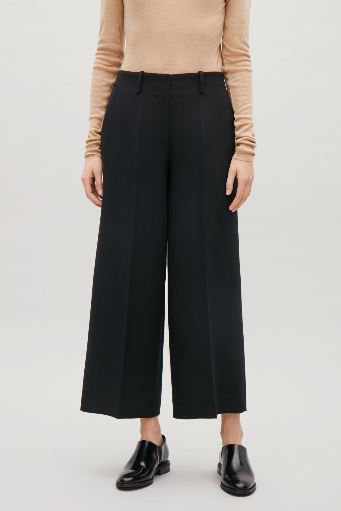 5ae90ce1d223a Model side image of Cos tailored wool culottes in black