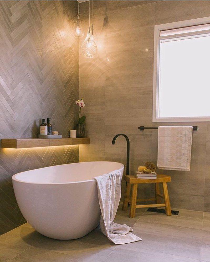 White stand alone bath tub, black tap and towel tack, timber shelf ...