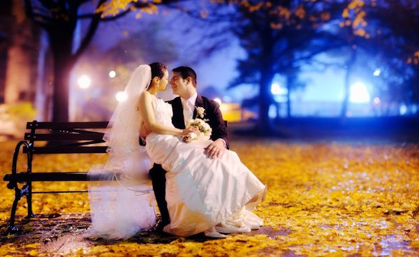 bride sitting on grooms lap - seated on a bench - yellow leaves covering the moist ground with a blue mistic glow in the backgound -  photo by New York City based wedding photographer Ryan Brenizer