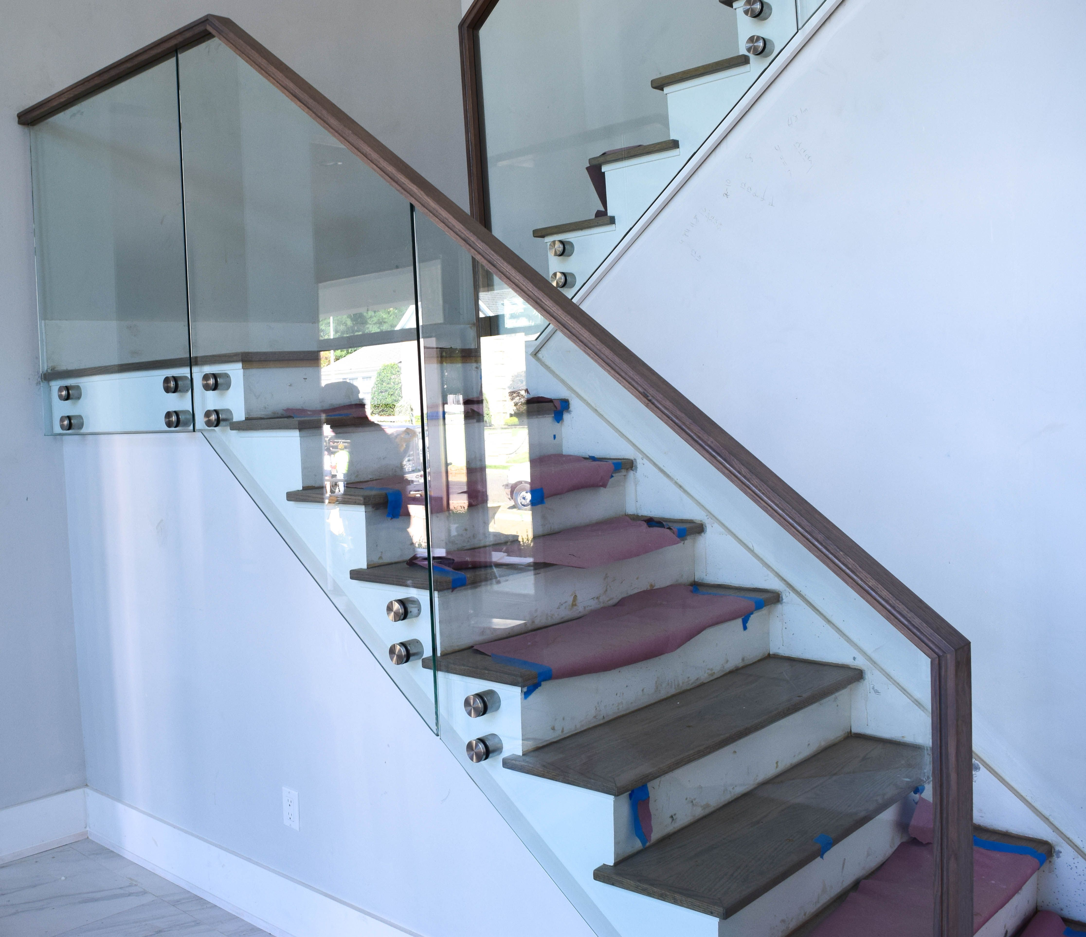 Modern glass railing with stainless steel standoffs and wood top
