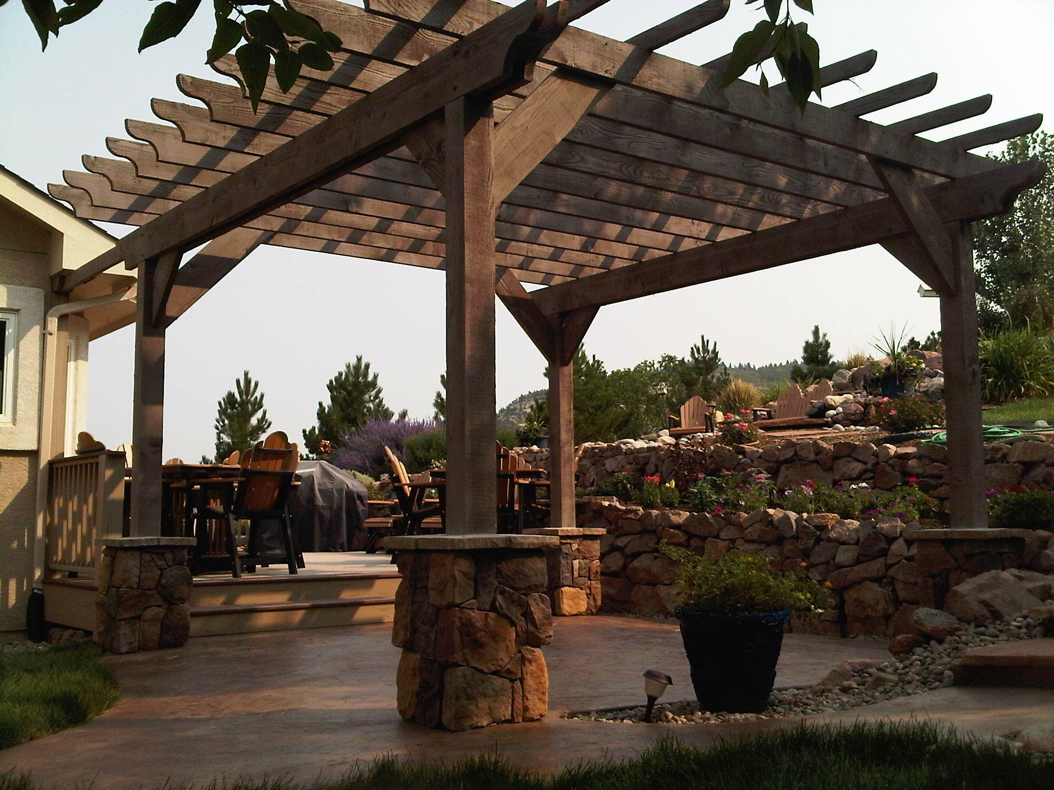 Rough Sawn Timber Pergola, Stone Veneer Post Bases, Stamped Concrete Patio,  Tiered Rock