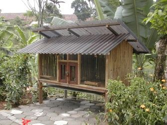an outdoor duplex rabbit hutch in tropical country the wall and the floor are made