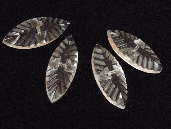 A set of four unique carved art deco glass buttons, approx. 1.25 long, 3/4 wide, just under 1/4 thick. Very special item, I have never seen