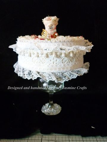 A recycled biscuit tin and sherry glass using lace and fabric flowers and gems