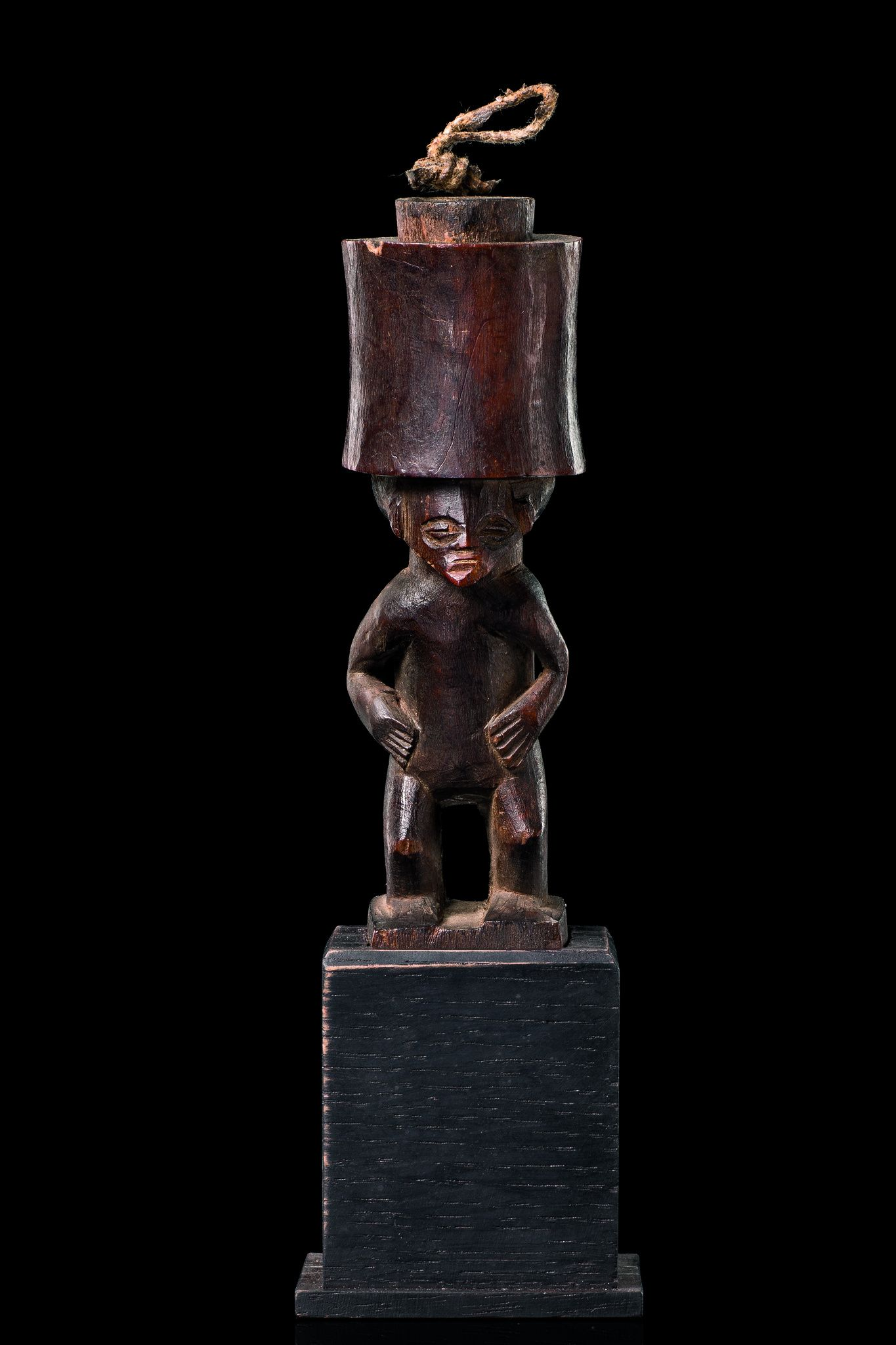 Figuraler Behälter für Schnupftabak D. R. Kongo, Chokwe Holz, braune, leicht glänzende Patina, Kopfaufsatz als Behälter, separat gearbeiteter Verschlußstöpsel, min. besch., leichte Gebrauchsspuren, Sockel; die Chokwe und verwandte Stämme rauchten Tabak oder schnupften ihn in rituellem Kontext um das Andenken an Ahnen zu ehren.