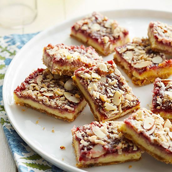 Raspberry Cheesecake Bars: Layers of cheesecake, raspberry filling, almonds and coconut form dessert bars perfect for summer. Recipe: http://www.midwestliving.com/recipe/cookies/raspberry-cheesecake-bars/