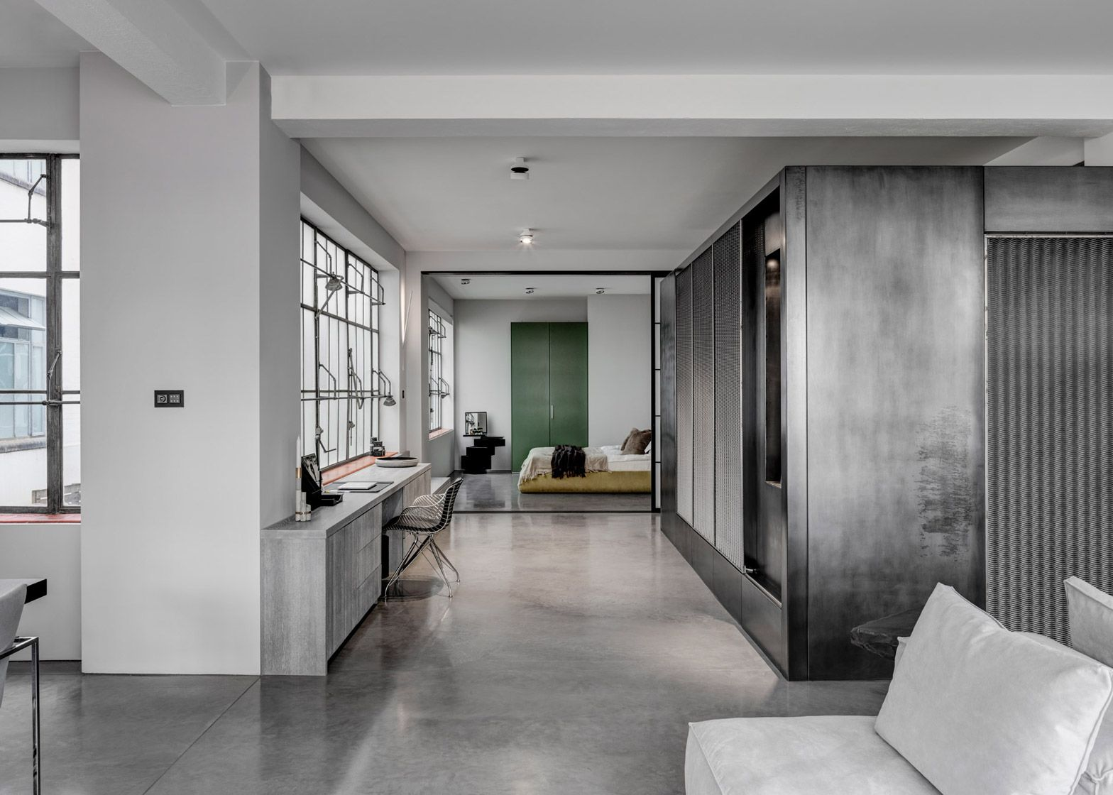 APA has transformed a London warehouse space into an apartment for two film directors, adding a raw steel volume that houses a movie archive and bathroom