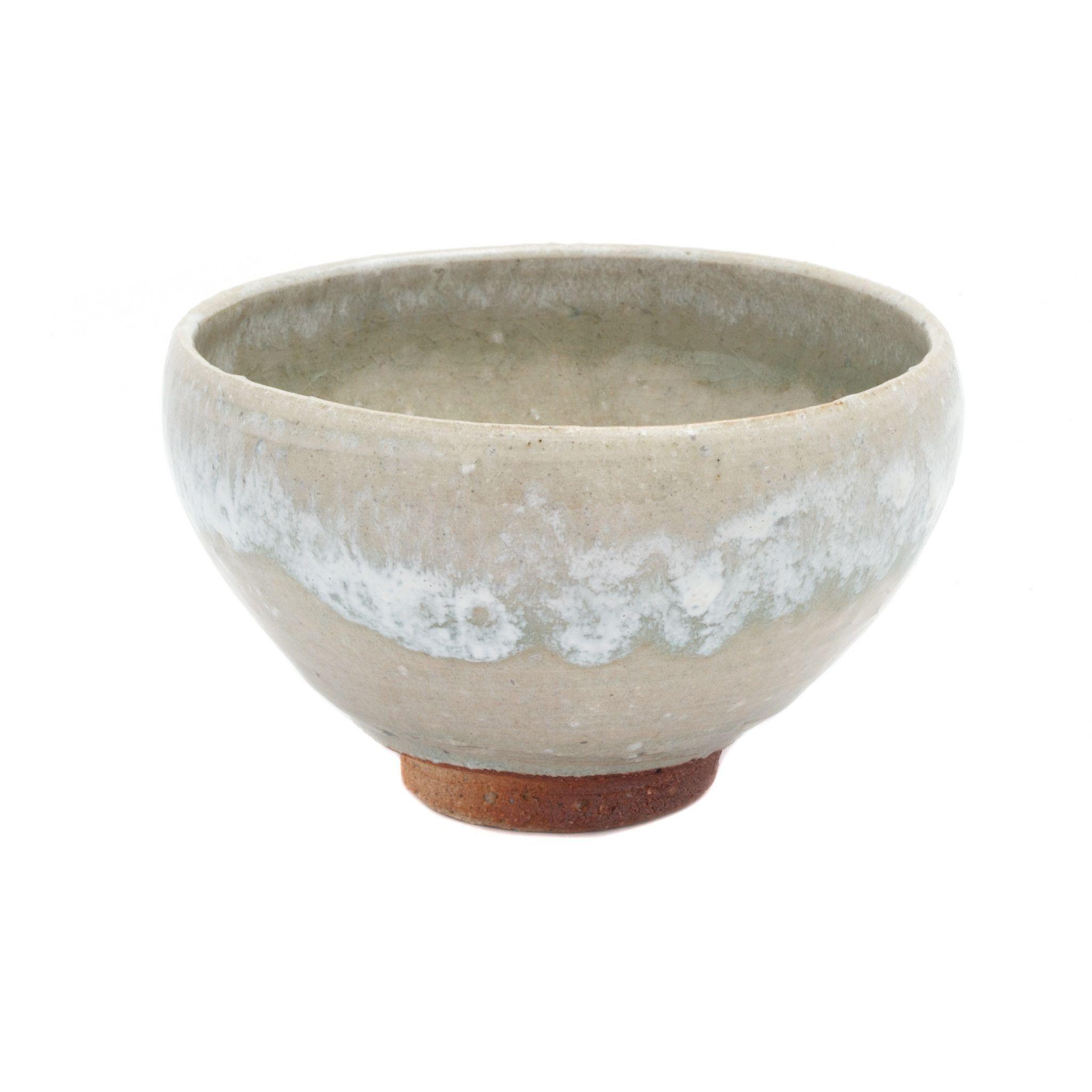 Origin: Mashiko, Japan Mashiko tea bowl made by Mingei artist Ishikawa Hajime. Beautiful glazing drips all around and inside and exposed earth foot at the bottom. Slightly rounded body.