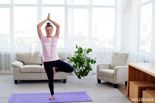 portrait of young woman practicing balance yoga asana