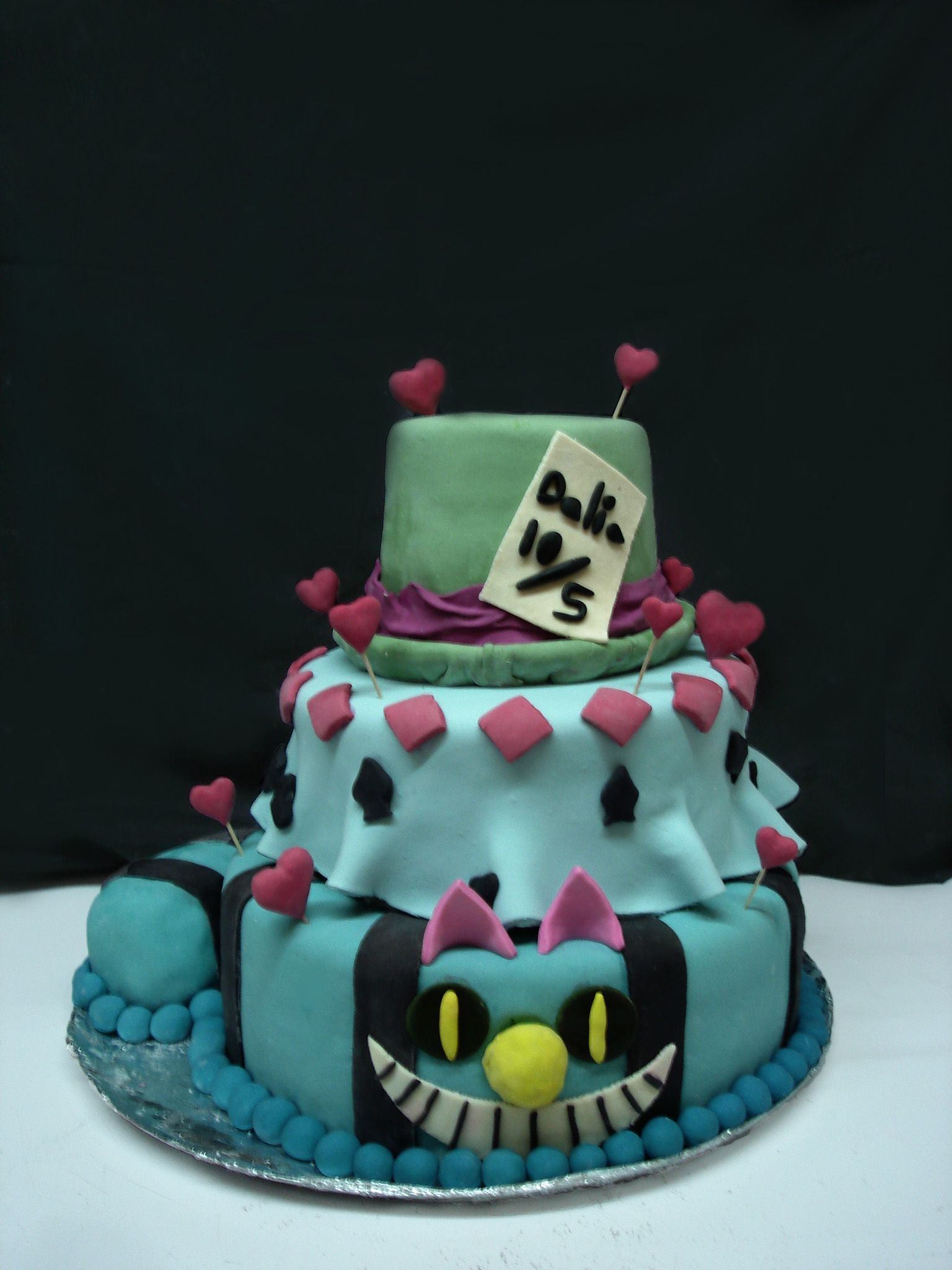 A cake for the quinceañera with alice in wonderland theme alice in