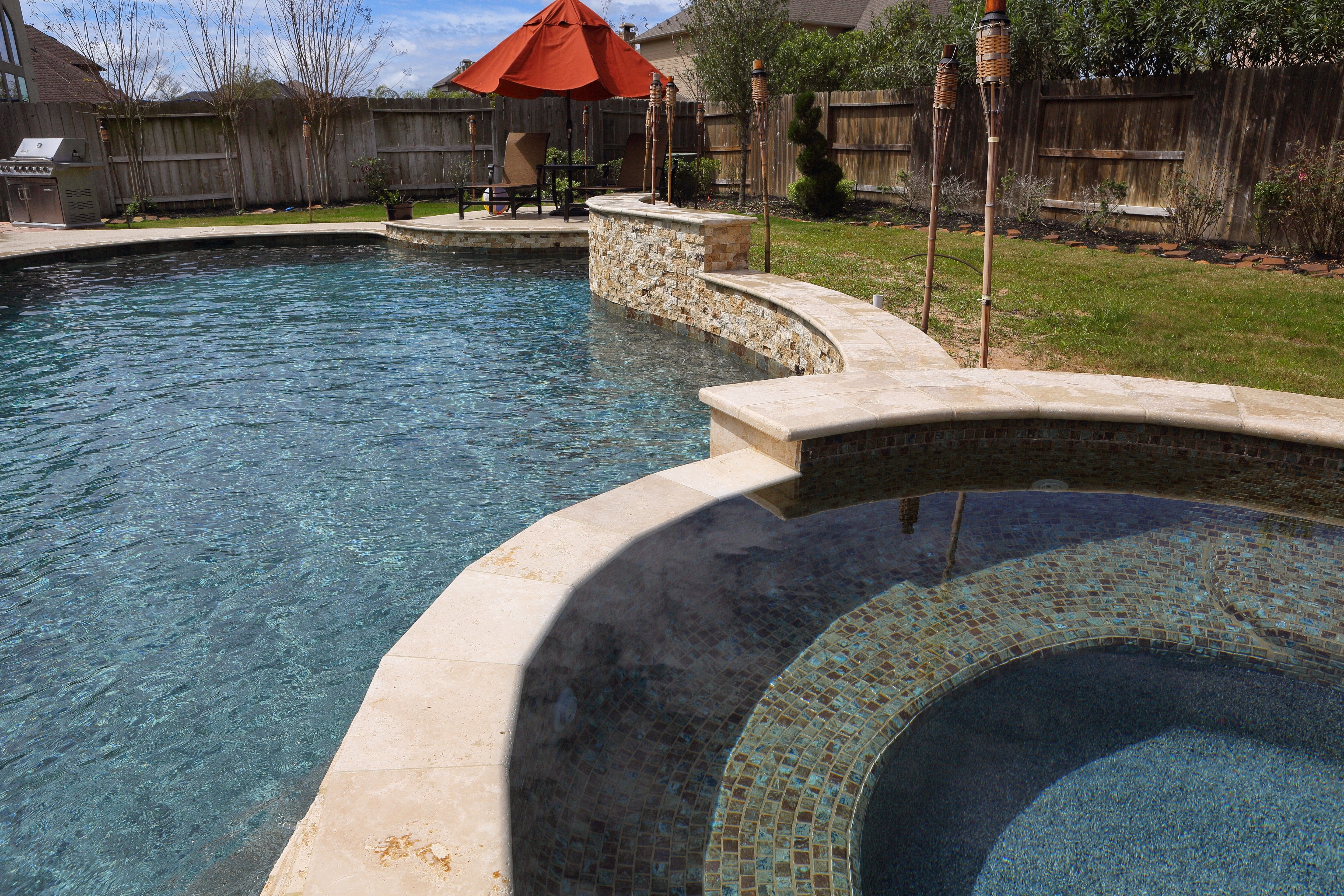tiled spa with tiered travertine spillover and scabos swimming
