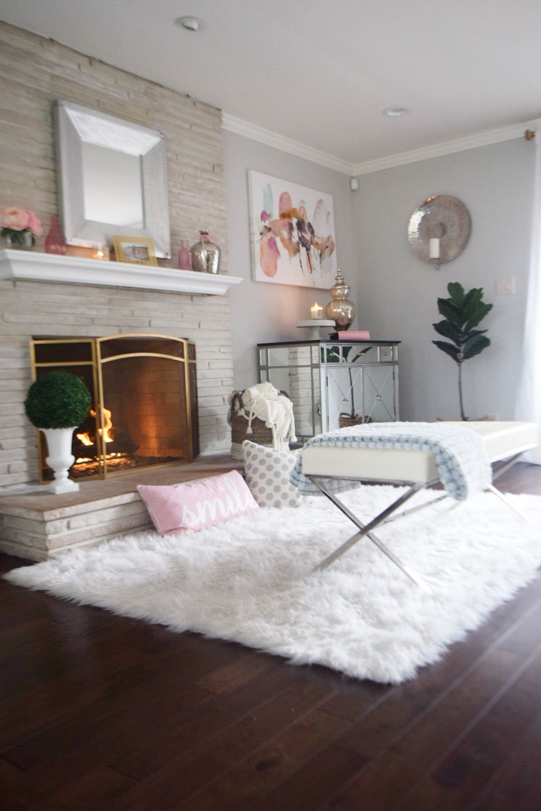 A faux fur rug, cozy throws and pillows make for the perfect spot