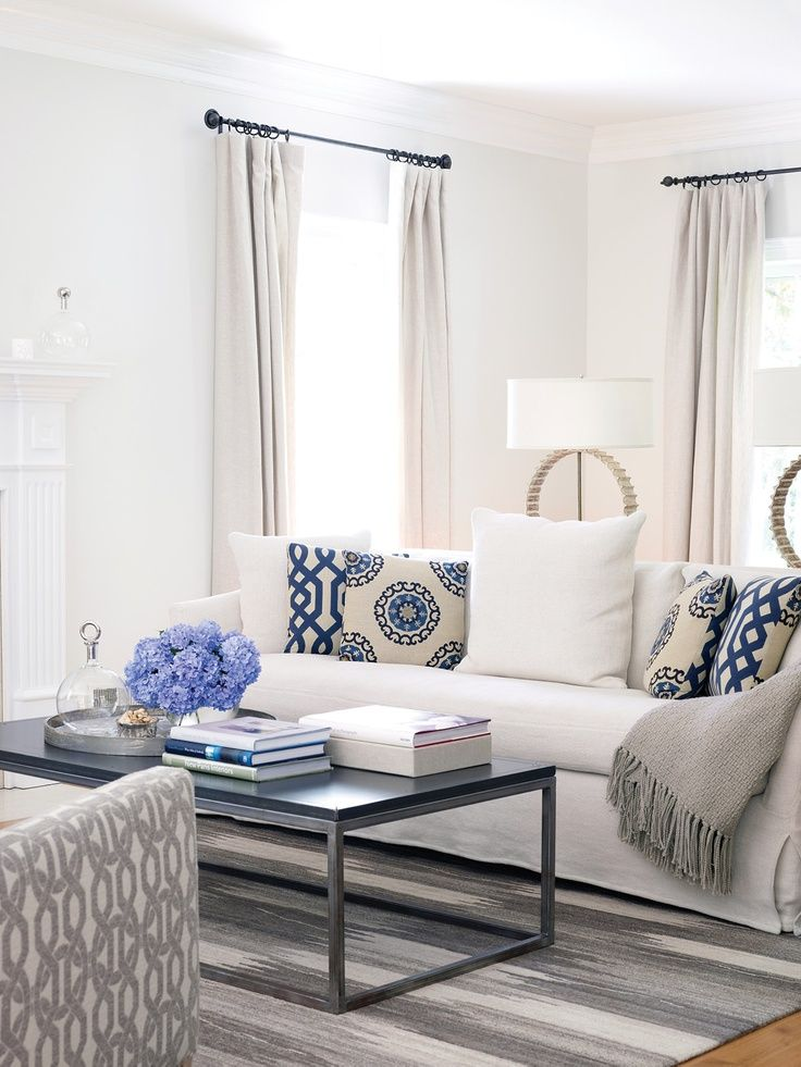 transitional white living room with white sofa, blue pillows and - wohnzimmer grau taupe