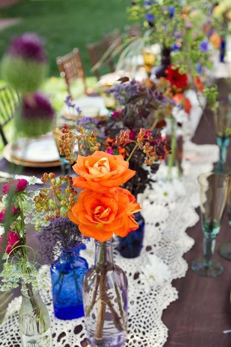mismatched bottles and a variety of flowers as a table center piece.