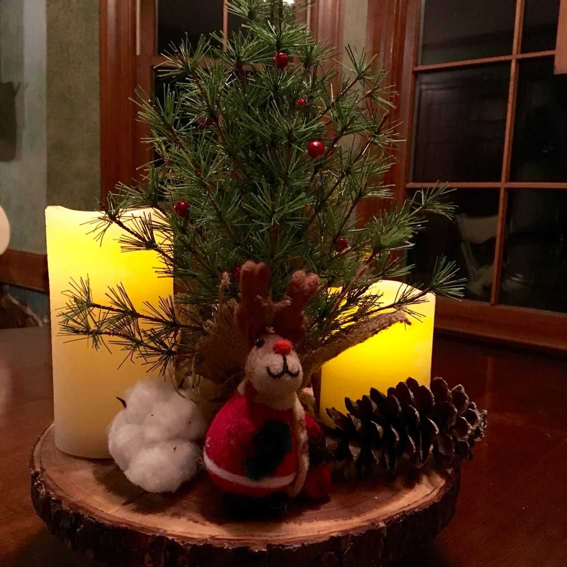 Christmas Felt Ornaments on natural wood pedestal with mini tree, pine cone, candles and cotton bloom.