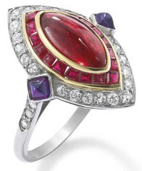 A ruby, diamond and sapphire ring. The central oval cabochon ruby set within a calibre-cut ruby cluster to a further brilliant-cut diamond cluster accented to the shoulders by similarly cut diamonds and sugarloaf sapphire points, ring size M. Via Phillips.
