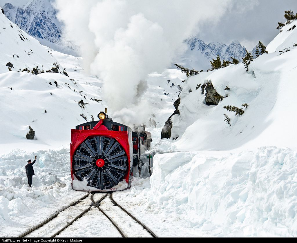 Entering White Pass. Having just switched his passenger extra onto White Pass Siding, Brakeman Dave Dobbs lines the switch and signals for the Rotary Fleet to come out of the cut and into White Pass Station. This shot was taken on the second day of the 2011 spring plowing operation, when the main and siding in front of the station had been cleared, but everything north of that remained snowbound, with average snow depths over the next mile or so of track at about 10 feet and drifts roughly…
