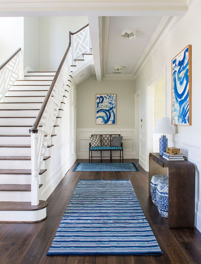 Beautiful Foyer With Blue And White Decor Dark Hardwood Floors Wall Wainscoting And Custom Staircase Railing House Design Beach House Design Interior Design