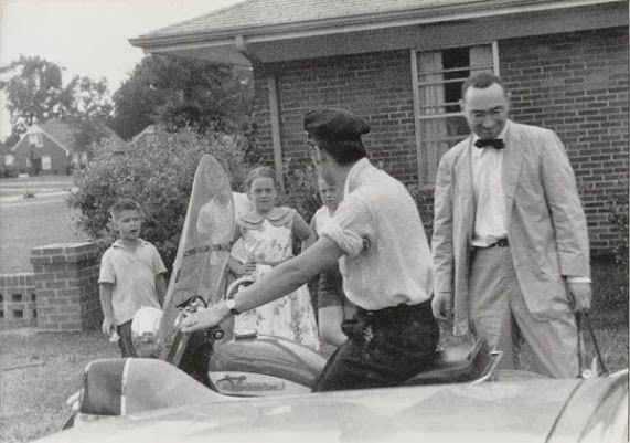 Elvis preparing to take a ride while neighborhood kids watch in the driveway  (May 1956) (Photo by Marvin Israel)