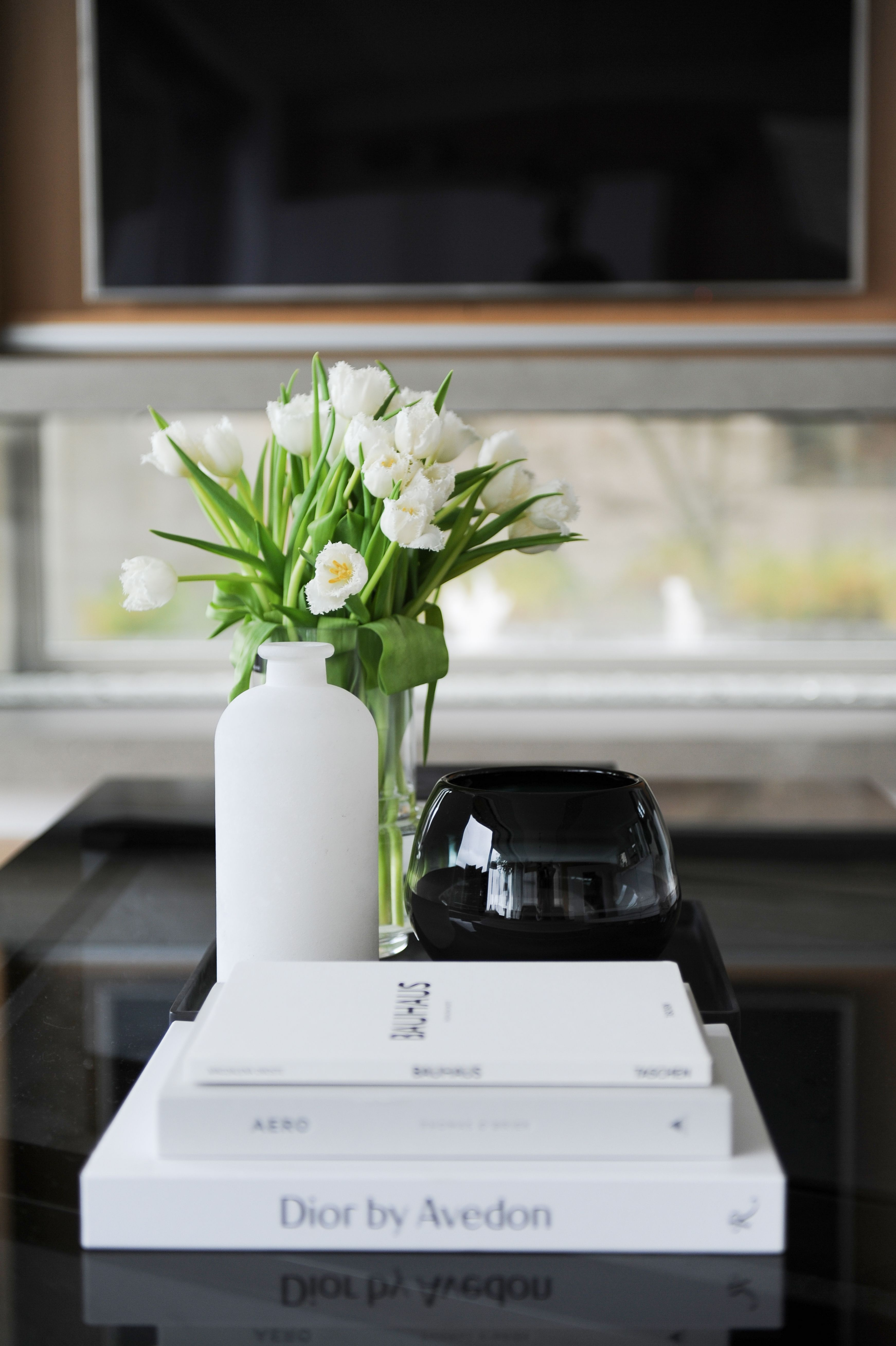 Transforming and setting the mood is about the details. Books, flowers, vases are just a few items that are great on coffee tables.  Like this black glass coffee table.