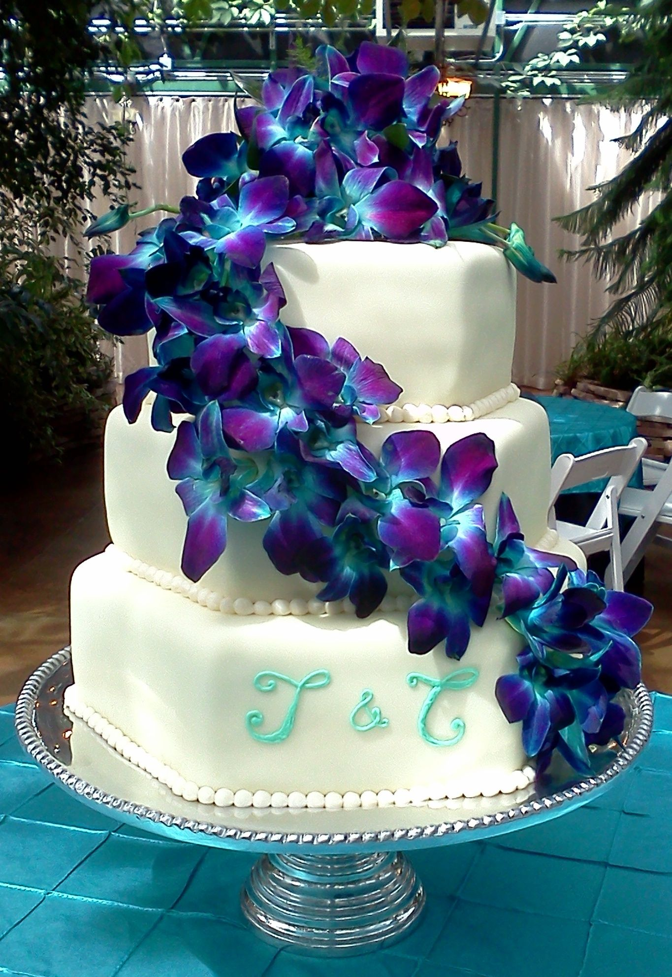 Three tiered wedding cake with blue orchids trailing down
