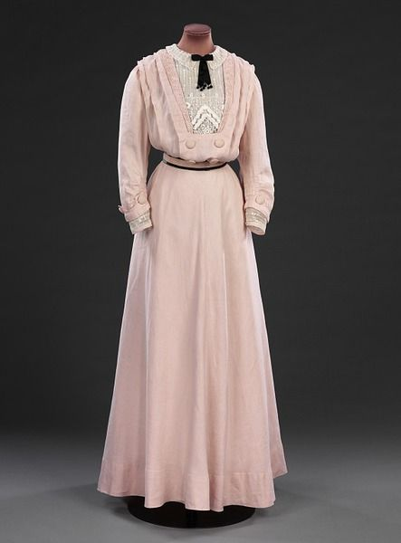 Day Dress, Britain, 1908: This pink linen dress bears no makers label, but is likely to be made by a high end dressmaker of the sort employed for less important and less costly gowns. The centre front of the skirt is cut on the cross, giving a graceful hang to the fabric and the dress is trimmed with cotton braid and embroidered striped net.