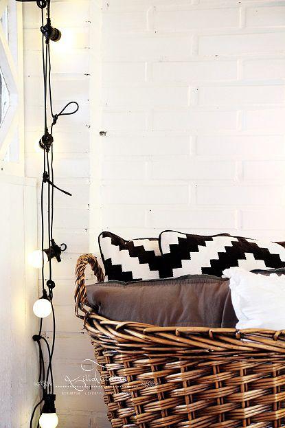 Lights & a basket full of pillows beside the fireplace