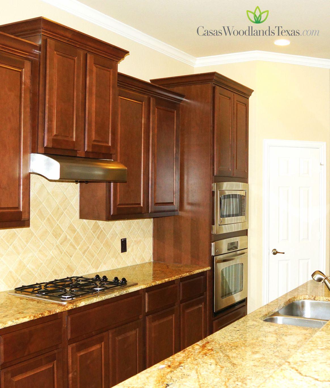 La cocina est equipada con gabinetes de madera for Gabinetes de madera para cocina pequena