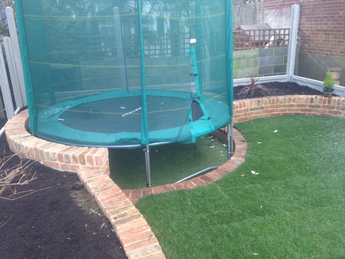 Trampoline semi sunk with a astroturf under for added play