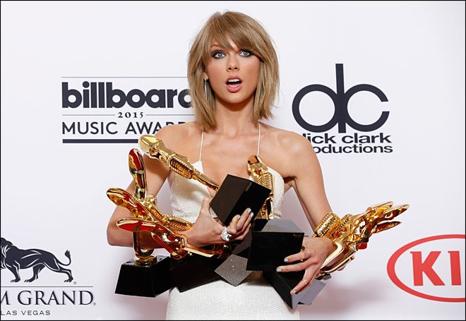 """Taylor Swift poses in the press room with the awards for top Billboard 200 album for """"1989,"""" top female artist, chart achievement, top artist, top Billboard 200 artist, top hot 100 artist, top digital song artist, and top streaming song (video) for """"Shake It Off"""" at the Billboard Music Awards at the MGM Grand Garden Arena on Sunday, May 17, 2015, in Las Vegas. (Photo by Eric Jamison/Invision/AP)"""