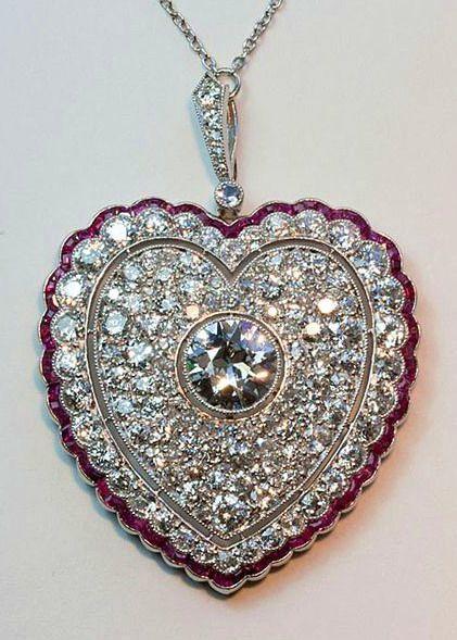 A large Edwardian diamond and ruby heart  platinum pendant, set with caliber cut rubies, a border of old cut diamonds.