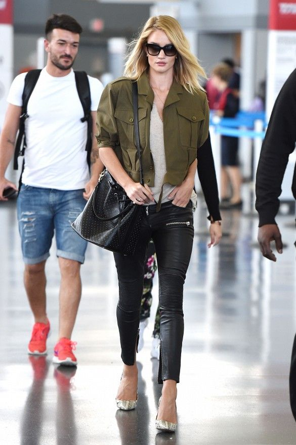 Rosie Huntington-Whiteley wears a cropped army jacket, t-shirt, leather biker pants, bucket bag, and snakeskin pumps