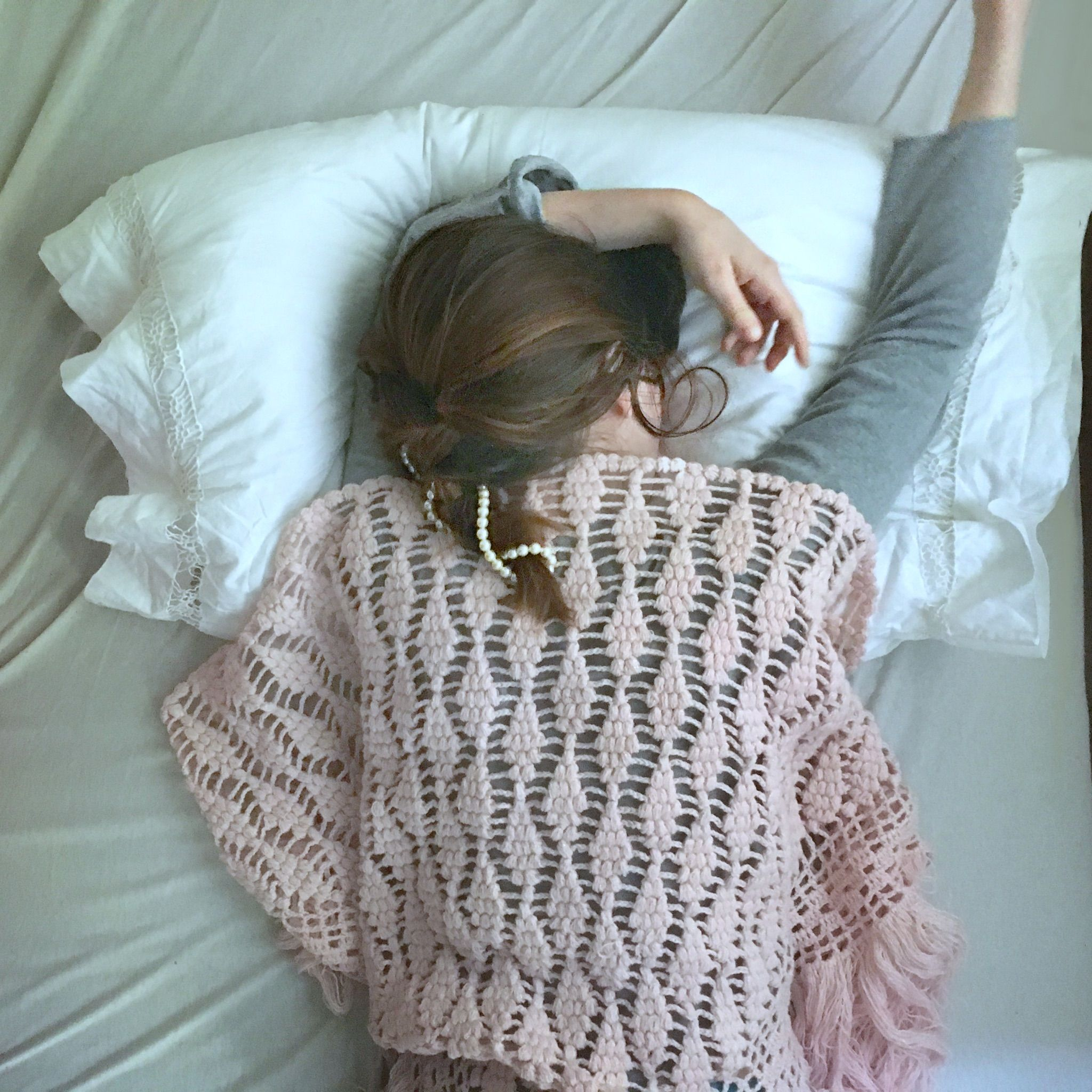 Pink shawl & pearls in bed.