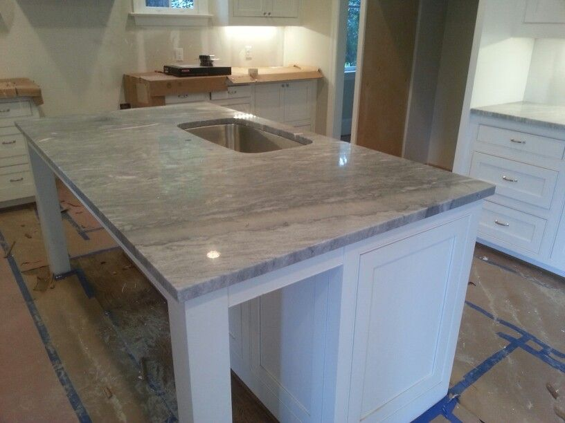 Sleek kitchen island features Sky White quartzite, with grey, white, and blue tones, giving this kitchen remodel a contemporary feel and functional design.